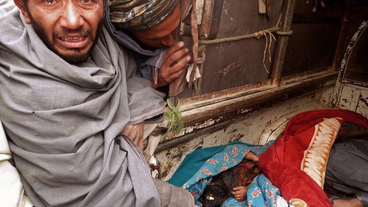 Deux Afghans pleurent les civils tués le 11 mars 2012 par un soldat américain dans la province de Kandahar. (JANGIR / AFP)
