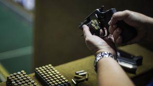 """Un homme prépare son arme au club de tir """"Calibre 12"""" à Sao Goncalo, à Rio de Janeiro, au Brésil, le 3 septembre 2018. (DANIEL RAMALHO / AFP)"""