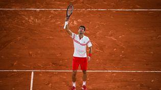 Novak Djokovic lève sa raquette au ciel après sa victoire en demi-finale de Roland-Garros 2021 contre Rafael Nadal au terme d'un match d'exception le 11 juin 2021 (CHRISTOPHE ARCHAMBAULT / AFP)