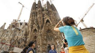 Des touristes devant la basilique de la Sagrada Familia, à Barcelone, le 3 octobre 2017 (PAU BARRENA / AFP)