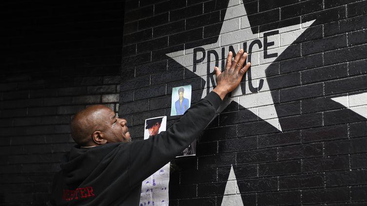 """Un fan touche, jeudi 21 avril, le nom de Prince peint sur un des murs de """"First Avenue"""", la boîte de nuit de Minneapolis où a débuté la star. (CRAIG LASSIG / REUTERS)"""