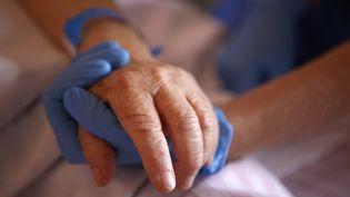 Une infirmière portant un gant de protectiontient la main d'une patiente de l'unité de soins palliatifs à l'hôpital Eugénie d'Ajaccio en Corse, le 23 avril 2020. (PASCAL POCHARD-CASABIANCA / AFP)