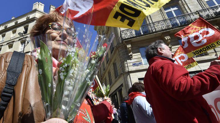 Une femme tient un bouquet du muguet lors d'une manifestation syndicale, le 1er mai 2016, à Bordeaux (Gironde). (GEORGES GOBET / AFP)