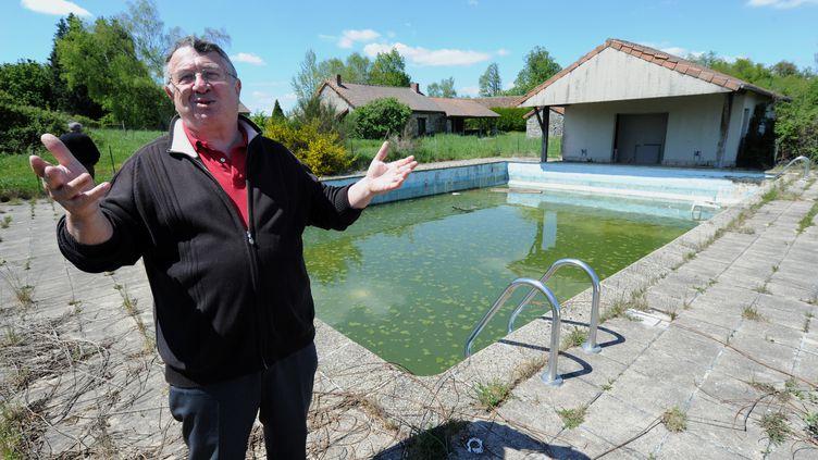 Le maire de Saint-Nicolas-Courbefy, Bernard Guilhem, se tient le 16 mai 2012 devant la piscine du hameau de Courbefy, mis en vente aux enchères le 21 mai. (PASCAL LACHENAUD / AFP)