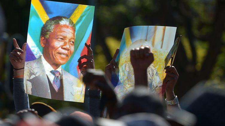 Le portrait de Nelson Mandela porté par la foule, en signe de respect après la mort de l'ancien président sud-africain. (FILIPPO MONTEFORTE / AFP)