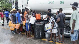 Des habitants viennent s'approvisionner en eau après le tremblement de terre qui a ravagé le sud-ouest d'Haïti, lundi 16 août 2021, à Camp-Perrin. (REGINALD LOUISSAINT JR / AFP)