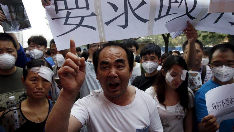 Des habitants de Tianjin manifestent, le 17 août 2015, en marge d'une conférence de presse des autorités municipales. (KIM KYUNG HOON / REUTERS)