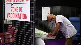 Un membre de l'équipe médicale prend des notes dans la zone de vaccination d'un centre installé à Garlan (Finistère), le 31 mai 2021. (FRED TANNEAU / AFP)