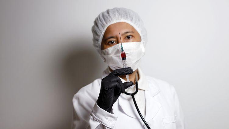 Un virologue pose avec une seringue de vaccination, le 19 avril 2020, à Nuremberg, en Allemagne. (CHRISTOPH HARDT / GEISLER-FOTOPRES / AFP)