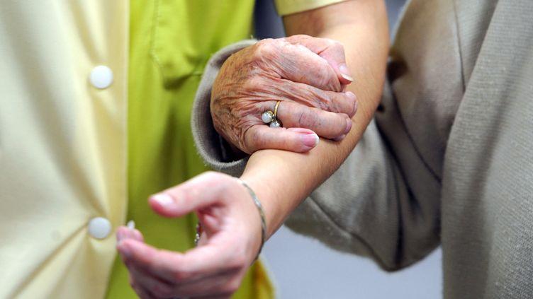 Une personne agée aidée par une femme. Photo d'illustration. (JEAN-FRANCOIS MONIER / AFP)