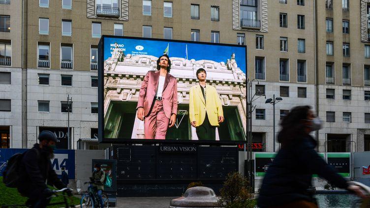 Dans le centre ville de Milan en Italie un écran permet de voir les collections masculine automne-hiver 2021-22, présentées dans le cadre de la Milan Fashion Week, le 15 janvier 2021 (MIGUEL MEDINA / AFP)