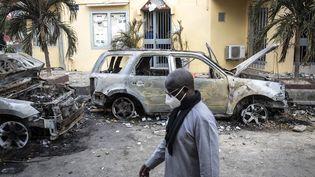Des personnes regardent les restes de deux voitures brûlées qui appartiendraità Radio Futures Media (RFM) à Dakar, au Sénégal, le 5 mars 2021. (JOHN WESSELS / AFP)