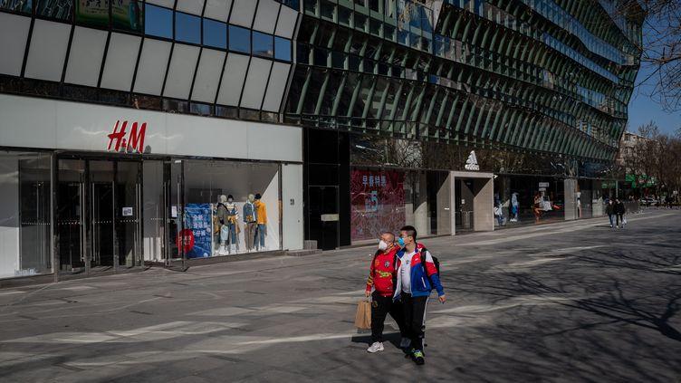 Le 19 mars 2020, deux hommes passent devant un magasin Adidas et H&M dans un centre commercial de Pékin (NICOLAS ASFOURI / AFP)