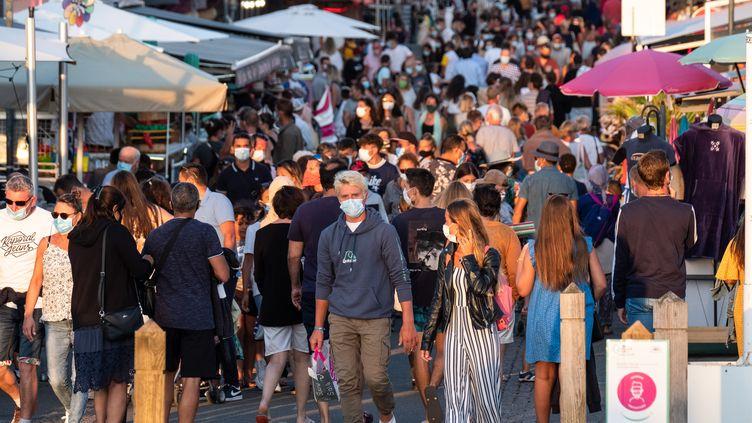 Des passants portant un masque dans une rue commerçante deBiscarrosse (Landes), le 14 août 2020. (VALENTINO BELLONI / HANS LUCAS)