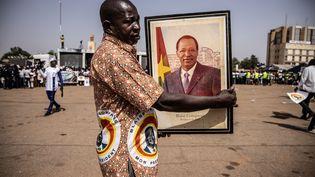 Un supporter du CDP, le parti de Blaise Compaoré, tient un portrait de l'ancien président déchu en exil, le 19 novembre 2020. (OLYMPIA DE MAISMONT / AFP)