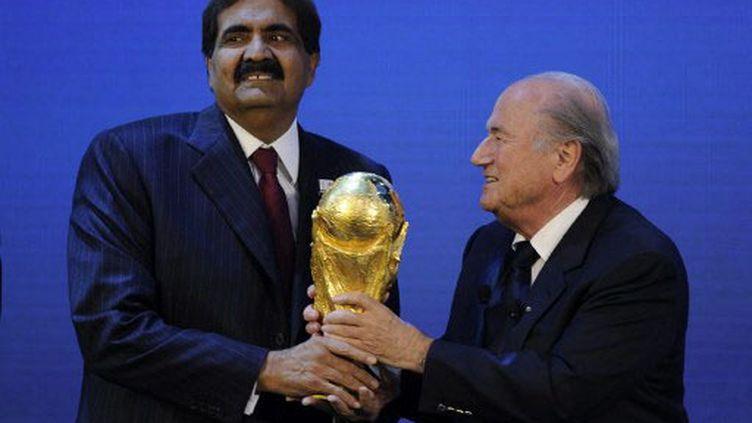 L'émir du Qatar, Hamad bin Khalifa Al Thani, reçoit le trophée Jules Rimet des mains de Sepp Blatter, président de la Fifa (PHILIPPE DESMAZES / AFP)