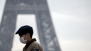 Un touriste porte un masque près de la Tour Eiffel à Paris, ce samedi 25 janvier 2020. Trois cas de personnes infectées par le coronavirus ont été identifées en France. Elles sont en cours de traitement. (MAXPPP)