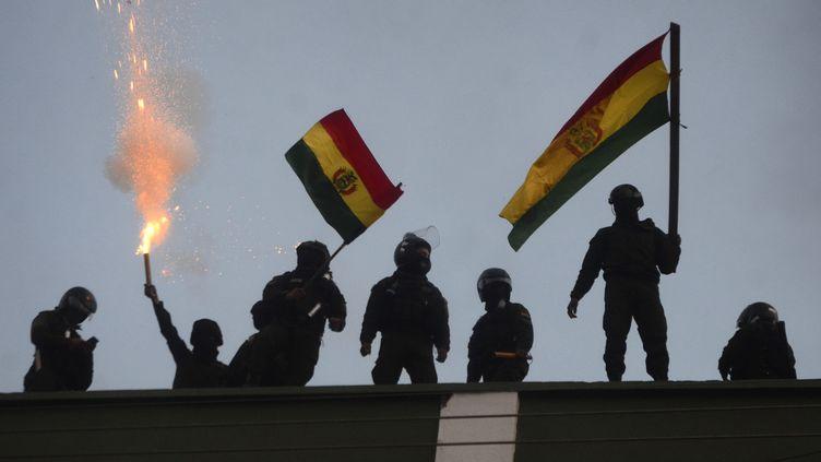 Des policiers opposés à la réélection d'Evo Morales lèvent un drapeau bolivien à Cochabamba, le 8 novembre 2019. (AP/SIPA)