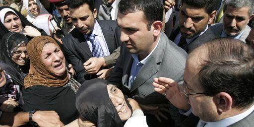 Le Premier ministre irakien,Nouri al-Maliki (à droite), discutant le 24-9-2009 à Bagdad avec des familles affectées par un attentat à la bombe. (Reuters - Saad Shalash)