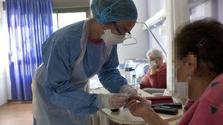 Une soignante d'une clinique de Montpellier apporte des soins à une résidente d'un Ehpad atteinte par le Covid-19, le 4 avril 2020 (illustration). (GUILLAUME BONNEFONT / MAXPPP)
