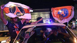 Des supporters du PSG fêtent la victoire du club face à Leipzig, en demi-finale de la Ligue des champions, le 18 août 2020 sur les Champs-Elysées à Paris. (BERTRAND GUAY / AFP)