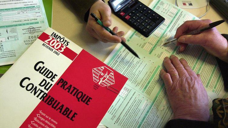 Une employée d'un centre des impôts aide une contribuable à remplir sa feuille de déclaration de revenus. (Photo d'illustration) (MYCHELE DANIAU / AFP)