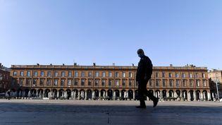 Un homme marche sur la place du Capitole à Toulouse, le 1er novembre 2020. (XAVIER DE FENOYL / MAXPPP)