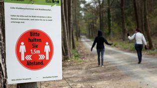 Un panneau surles règles de distanciation d'au moins 1,5 mètre à l'entrée d'une forêt à Berlin (Allemagne), le 15 avril 2020. (WOLFGANG KUMM / DPA / AFP)