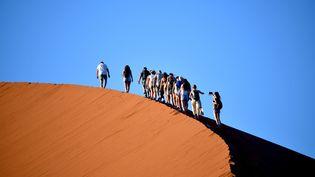 Des touristes sur la crête d'une dune dans le parc national Namib-Naukluft, dans le sud-ouest de la Namibie, le 1er mars 2019. (MATTHIAS TOEDT / DPA-ZENTRALBILD)
