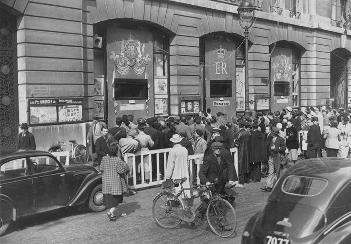 """Des Parisiens se pressent autourdesfenêtres du siège du """"Figaro"""" pour regarder le couronnement d'Elizabeth IIà la télévision, le 2 juin 1953 à Paris. (KEYSTONE / HULTON ROYALS COLLECTION / GETTY IMAGES)"""