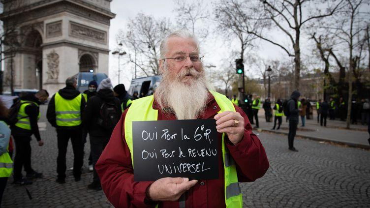 """Un manifestant """"Gilet Jaune"""" demande le revenu universel, le 8 décembre 2018 à Paris. (ALEXIS SCIARD  / MAXPPP)"""