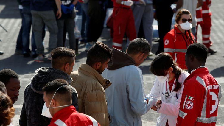 Une équipe de la Croix-Rouge vérifie la santé des migrants arrivés dans le port de Catane (Sicile), le 6 mai 2017. (DARRIN ZAMMIT LUPI / REUTERS)