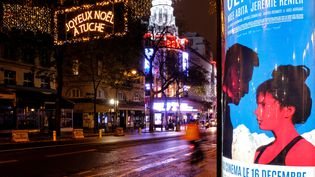 """L'affiche du film """"Slalom"""", dont la sortie était prévue le 16 décembre, près du cinéma Rex, à Paris, et une illumination souhaitant un joyeux Noël aux Tuches, en référence à la sortie reportée des """"Tches 4"""". (JOEL SAGET / AFP)"""