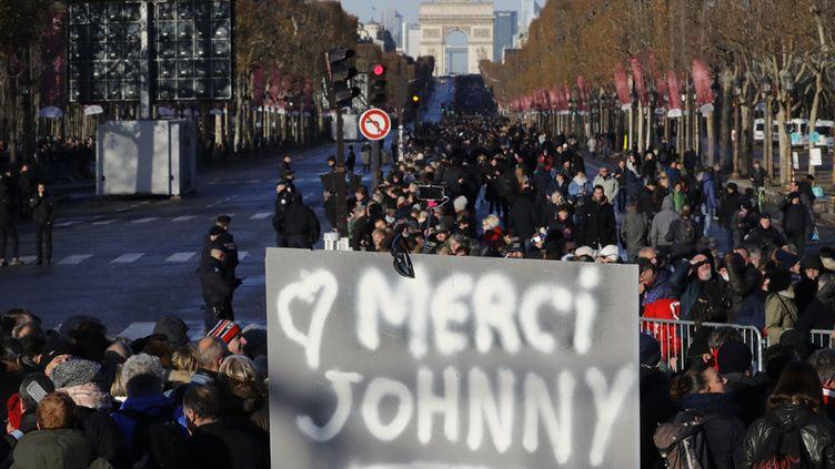 """Un panneau """"merci Johnny"""" brandi par l'un des nombreux fans qui attendent le passage du cortège funéraire de leur idole, samedi 9 décembre 2017 sur les Champs-Élysées  (Patrick Kovarik / AFP)"""