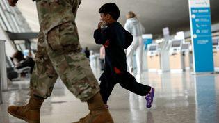 Un enfant afghan marche aux côtés d'un soldat américain lors d'une évacuation à l'aéroport de Kaboul, le 31 août 2021. (ANNA MONEYMAKER / GETTY IMAGES NORTH AMERICA / AFP)