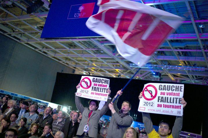 Des militants UMP brandissent des pancartes attaquant la gauche, lors du conseil national de leur parti, le 28 janvier 2012 à Paris. (LIONEL BONAVENTURE / AFP PHOTO)
