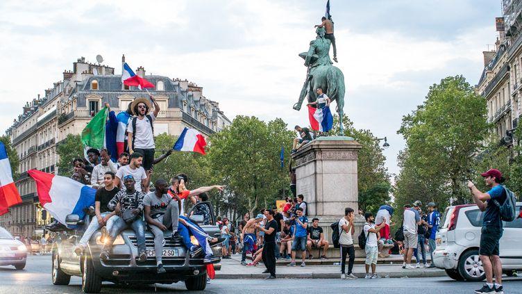 Des supporters fêtent la victoire de la France en Coupe du monde de football, le 15 juillet 2018 à Paris. (SIMON GUILLEMIN / HANS LUCAS / AFP)