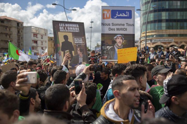 Des manifestants brandissent des slogans contre la chaîne Ennahar etSaïd Bouteflika, frère de l'ancien président, à Béjaia le 22 mars 2019. (SOFIANE BAKOURI / HANS LUCAS)