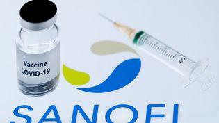 """Le logo de Sanofi, une seringue et un échantillon estampillé """"Vaccin Covid-19"""". (JOEL SAGET / AFP)"""