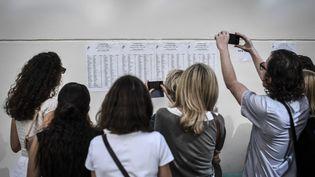 Des lycéens consultent les résultats du bac, le 5 juillet 2019 à Paris. (STEPHANE DE SAKUTIN / AFP)