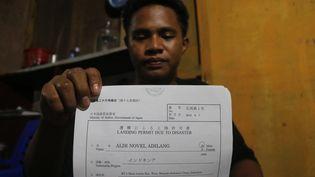 Le jeune Indonésien Aldi Novel Adilangmontre son permis d'accoster émis par le Japon, le 16 septembre 2018, àWori (Indonésie). (AFP)