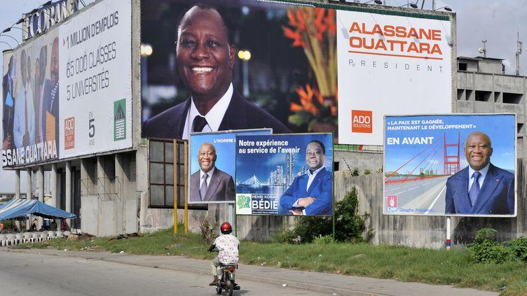 Cette photo prise le 23 octobre 2010 à Abidjan montre des affiches électorales représentantle président sortantLaurent Gbagbo (à droite et à gauche), l'ancien chef de l'Etat Henri Konan Bédié (au centre)et Alassane Ouattara (en haut, au fond), alors ancien Premier ministre, à la veille des élections présidentielles du 31 octobre. (SIA KAMBOU / AFP)