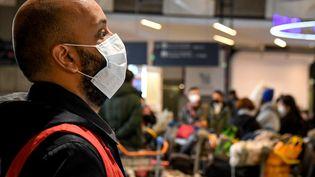 Un employé de l'aéroport Roissy-Charles-de-Gaulle, portant un masque, le 26 janvier 2020. (ALAIN JOCARD / AFP)