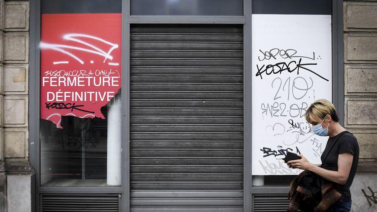 Une personne passe devant un magasin qui a fermé définitivement, le 8 juin 2020 à Paris. (ALAIN JOCARD / AFP)