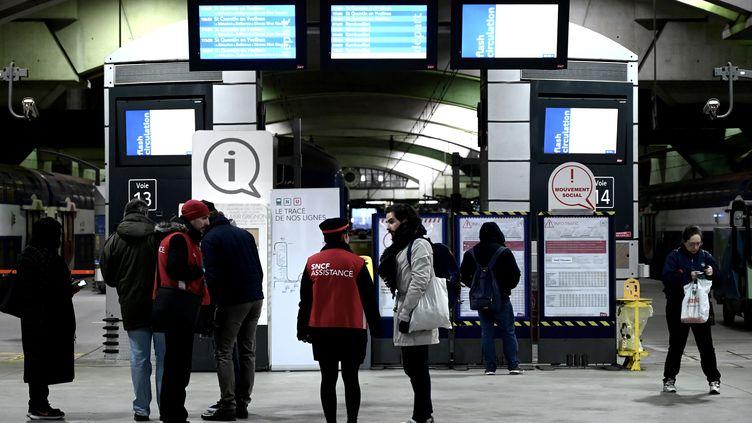 Des agents SNCF face à des voyageurs, en gare Montparnasse, à Paris, le 5 décembre 2019. (PHILIPPE LOPEZ / AFP)