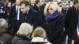 Le président de la République, Emmanuel Macron, et sa femme, Brigitte Macron, le 13 novembre 2017 devant le Carillon et le Petit Cambodge, avec des proches des victimes des attentats de Paris. (ETIENNE LAURENT / AFP)