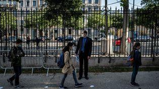 Des élèves d'un collège de Lyon (Rhône) retournent dans leur établissement après le déconfinement, le 18 mai 2020. (JEFF PACHOUD / AFP)
