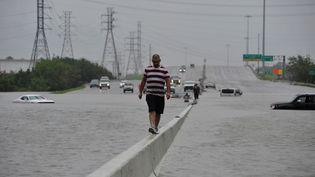 A Houston, cet automobiliste a abondonné sa voiture prise au piège des eaux et poursuit son trajet à pied. (NICK OXFORD / REUTERS)