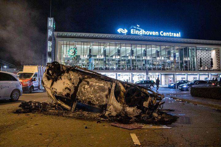 Une voiture a été incendiée par des opposants au couvre-feu, le 24 janvier 2021, devant la gare de Eindhoven (Pays-Bas). (NICOLAS ECONOMOU / NURPHOTO / AFP)