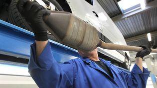 Un garagiste examine un pot d'échappement catalytique à Bordeaux (Gironde), le 13 mars 2013 (illustration). (LARTIGUE STEPHANE / MAXPPP)